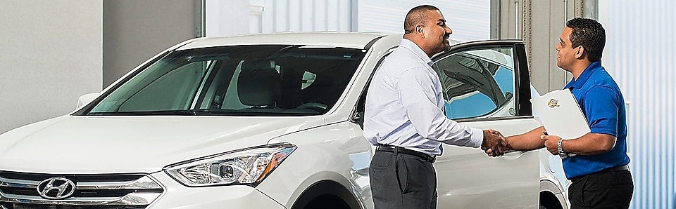 Two men shaking hands in front of a white Hyundai vehicle.